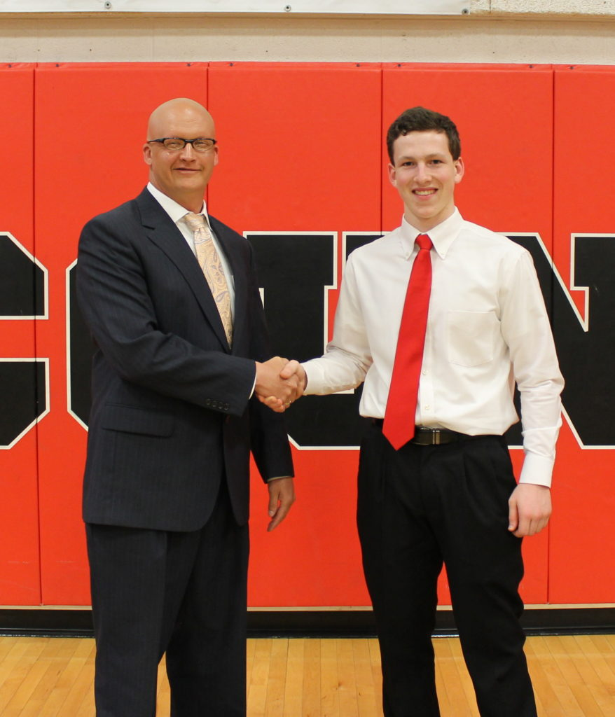 Nicholas Ruetter from the Farmers-Merchants National Bank presents Jeremy Steidinger with the 2018 FMNB scholarship.